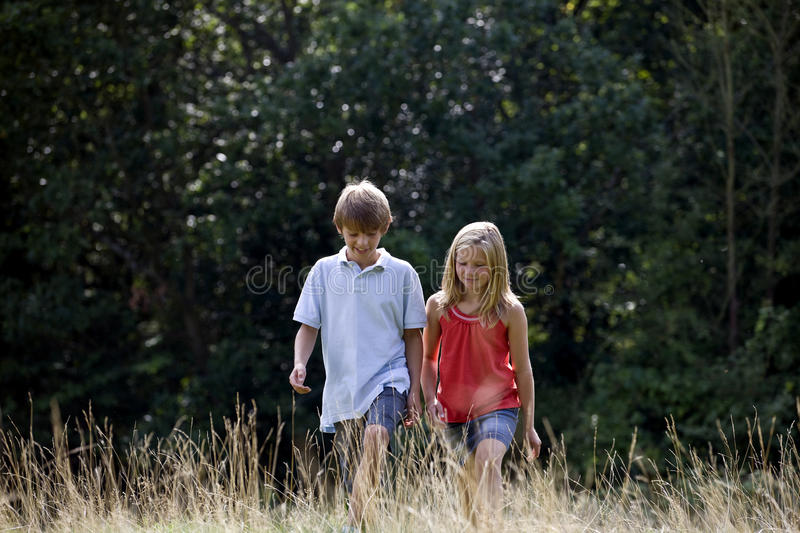 A young boy and girl walking through a field stock images