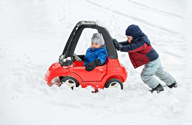 Young Boy Gives a Push to his Brother's Car Stuck in the Snow. A young boy dressed for cold weather sits in a red toy car stuck in the snow during the winter stock photo