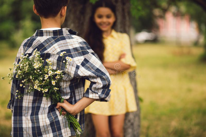 Little boy giving bouqet of flowers to girl. Young boy giving flowers to girl. Sweet little boy holding bouqet of flowers behind his back to give them to his stock images