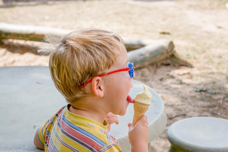 Young boy with glasess sits outside at table and eats ice cream stock images