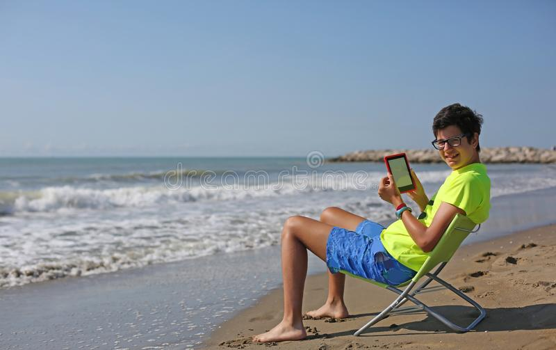 Boy with glasses reads an ebook on the beach by the sea in summe stock photos