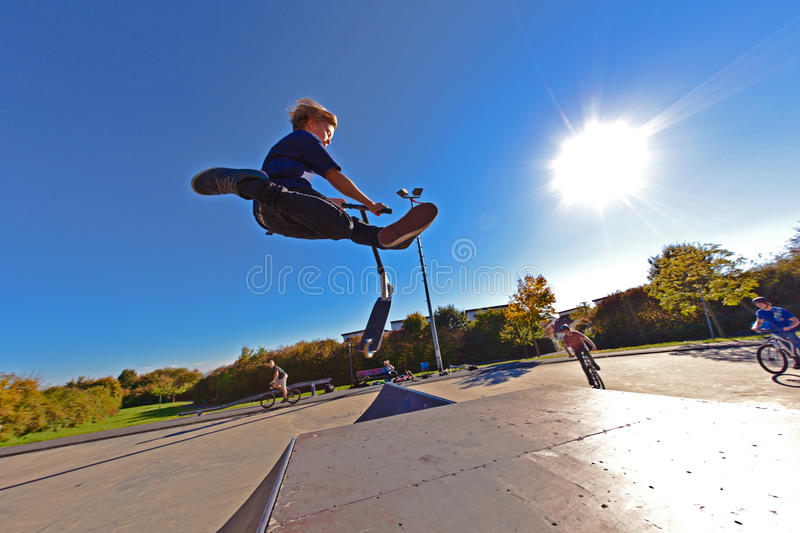 Young boy going airborne with scooter royalty free stock photos