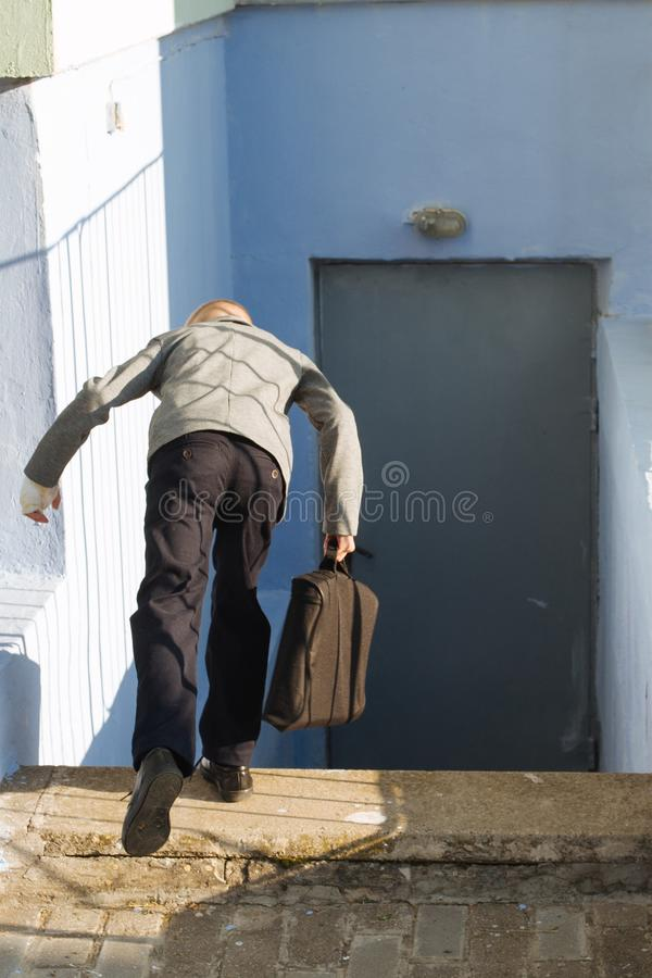 Young boy in a gray jacket with a briefcase falls from stairs edge down stock image