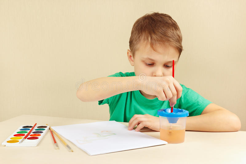 Young boy in green shirt painting with watercolors. Young boy in a green shirt painting with watercolors royalty free stock photos