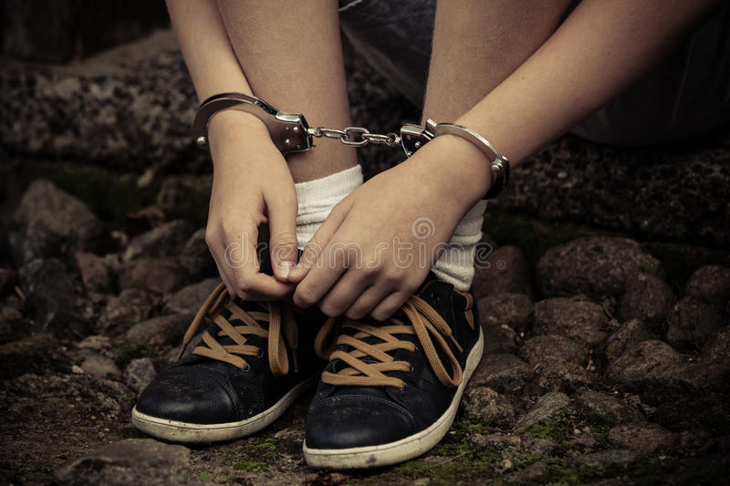 Young boy in handcuffs and sneakers royalty free stock image