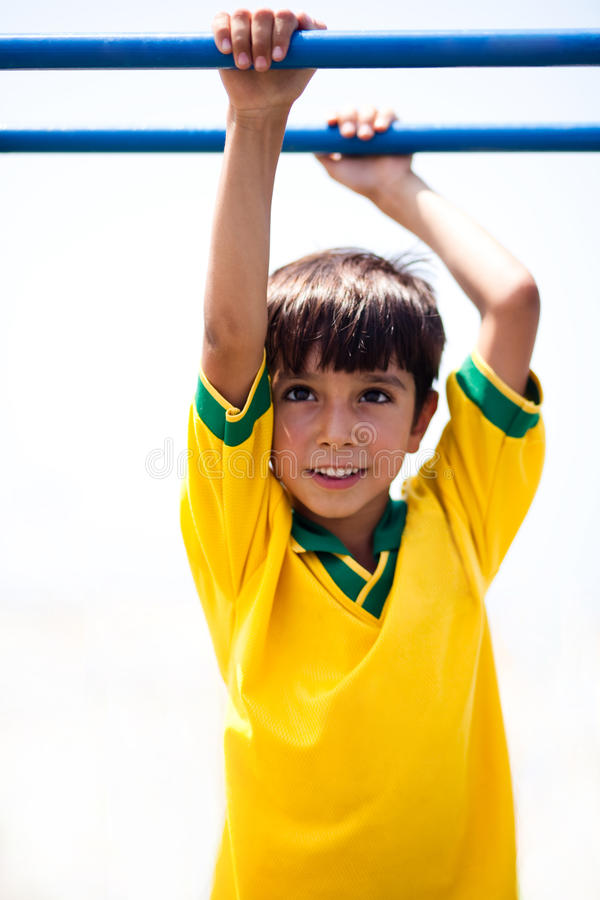 Young boy hanging on jungle gym stock image