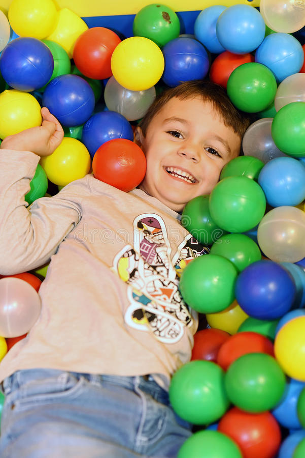 Young boy having fun in colored balls stock photo