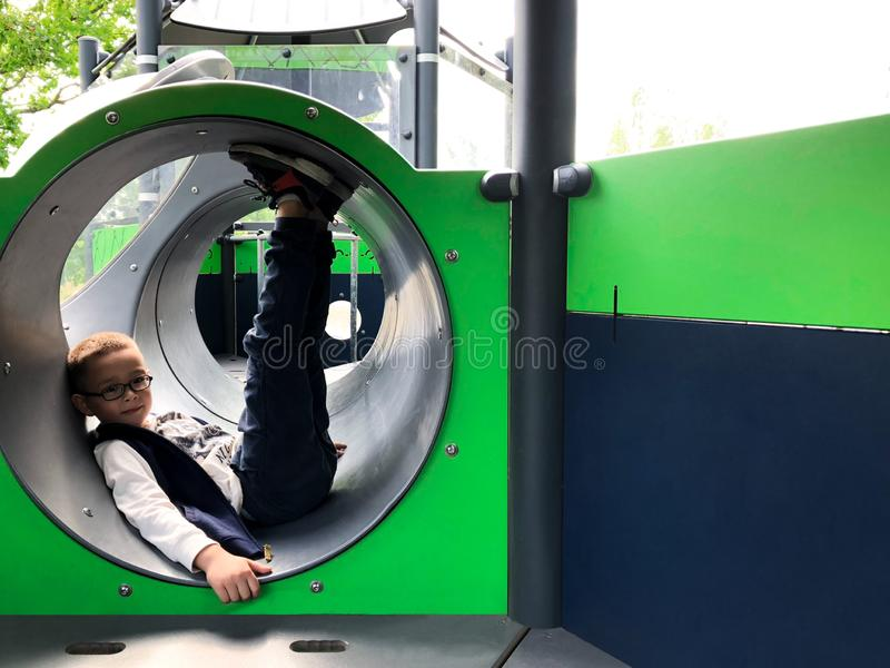 Young boy is having fun at the playground inside slide tube. Summer activity outdoors stock photos
