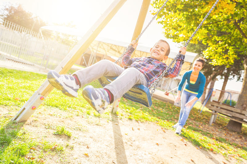 Young boy having fun on the swing royalty free stock images