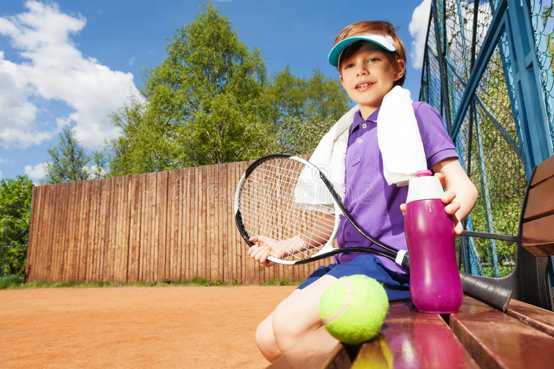 Young boy having rest after playing tennis stock photos