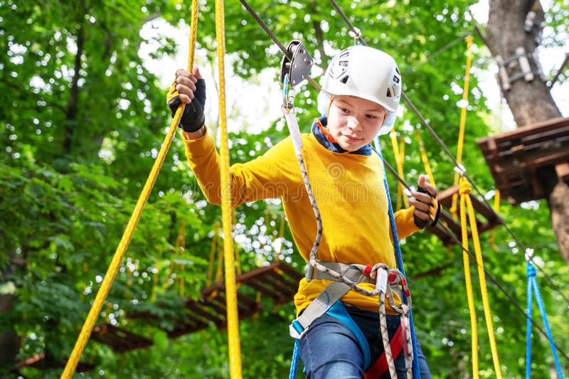Young boy in helmet in the rope park pass obstacles  route high among trees, extreme sport in adventure park stock photography