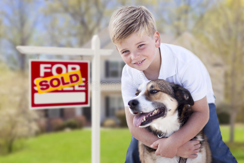 Young Boy and His Dog in Front of Sold For Sale Sign and House. Happy Young Boy and His Dog in Front of Sold For Sale Real Estate Sign and House stock photography