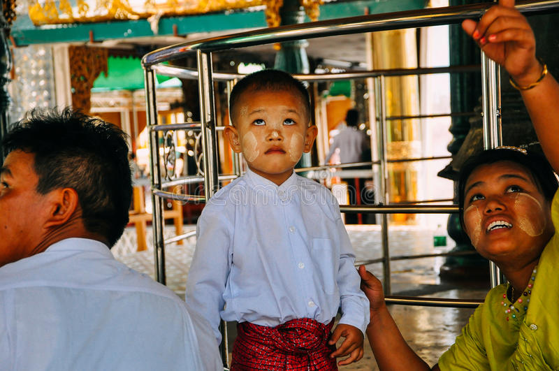 A young boy and his family in a temple at Shwedagon Pagoda in Yangon. royalty free stock image