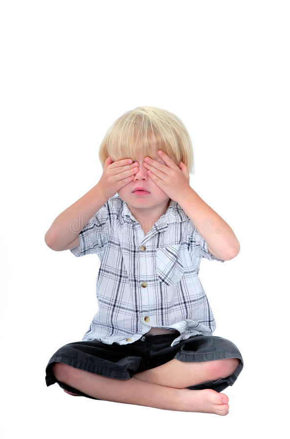 Young boy with his hands over his eyes and white background stock images