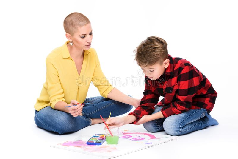 Young boy and his therapist in child occupational therapy session painting with watercolors. Child art therapy concept. Young boy and his therapist in child royalty free stock photos