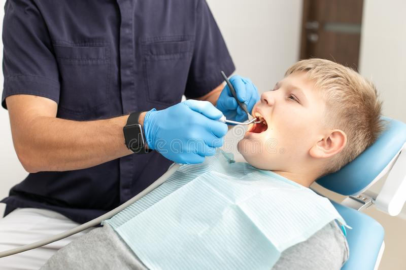 Young boy hold his mouth open while his doctor mothwashing it stock photos