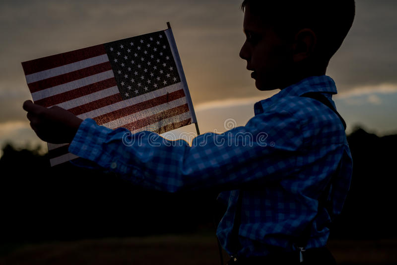 A young boy holding an American Flag, Independence Day. Silhouette of a young child holding an American flag, grateful for freedom royalty free stock photo