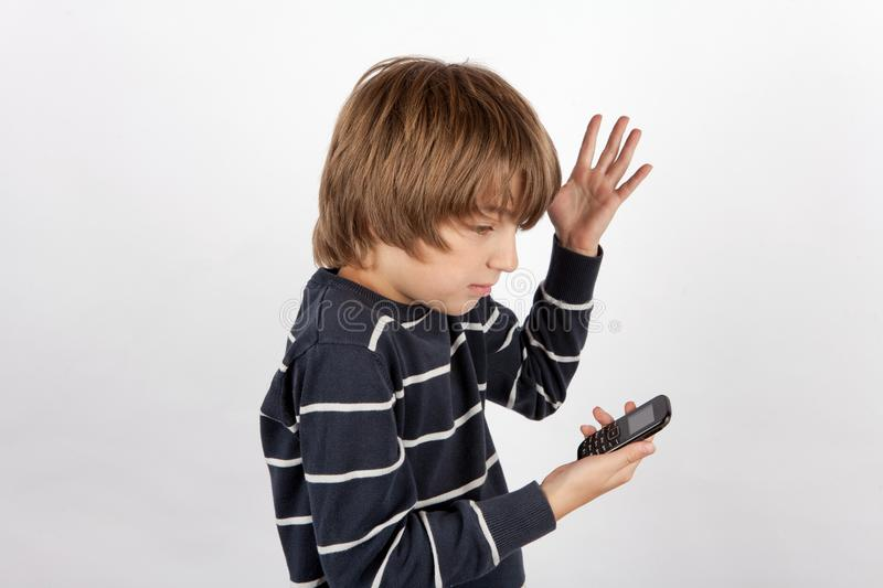 Young boy holding a basic mobile phone and not too happy with it royalty free stock photos