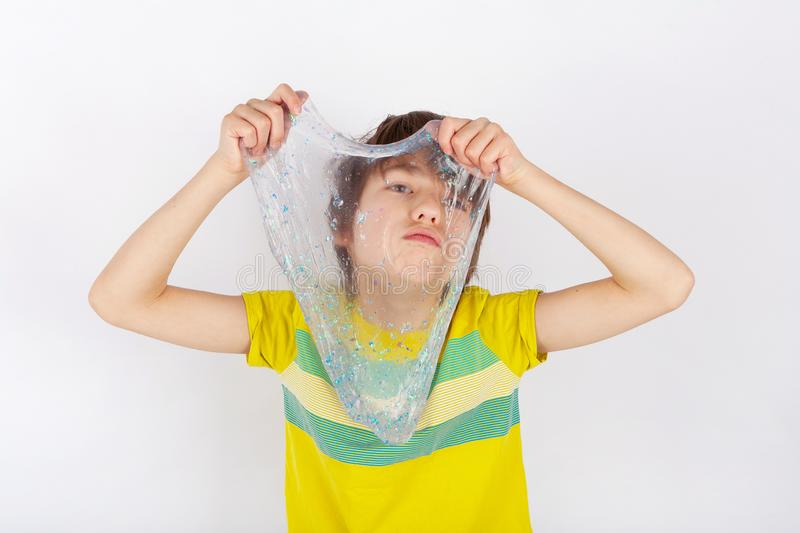 Young boy holding a glitter slime in front of him.  stock image