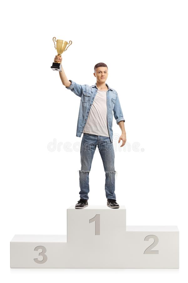 Young boy holding a gold trophy cup on a winner pedestal royalty free stock images