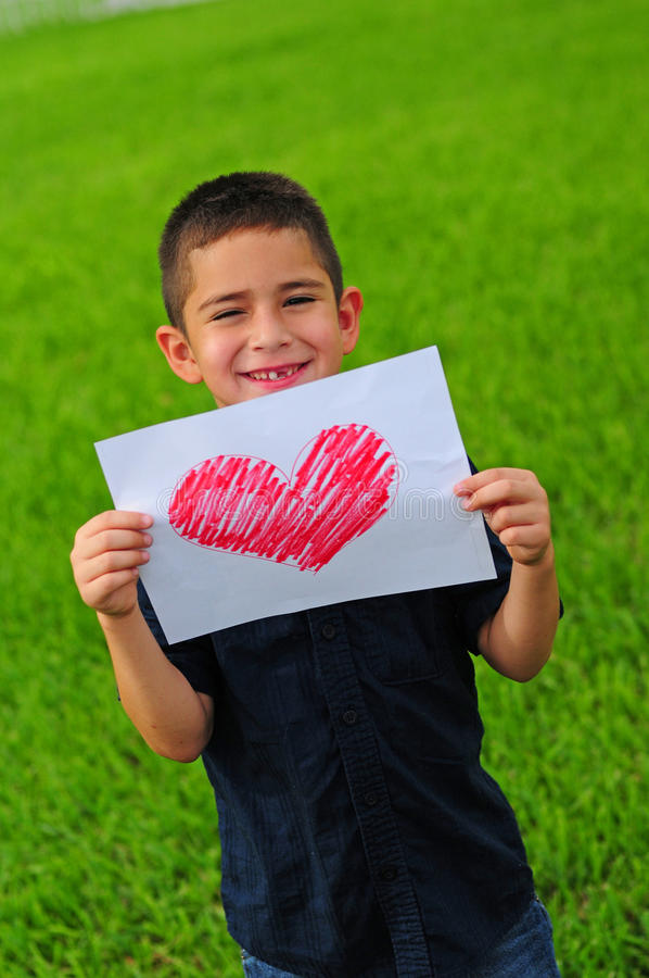 Young boy holding heart drawing. Young boy holding up a gift of a red heart drawing royalty free stock photo