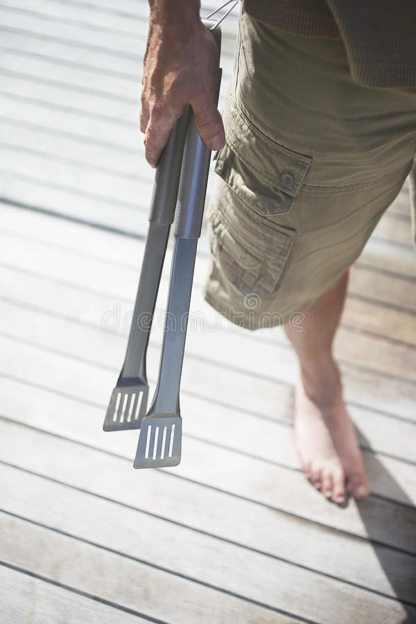 Young Boy Holding Kitchen Tongs royalty free stock photography