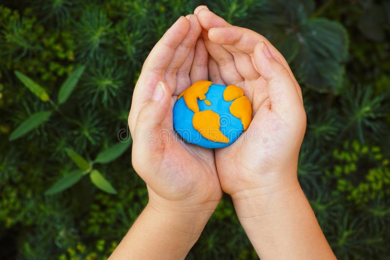 Young boy holding planet Earth in his hands royalty free stock image