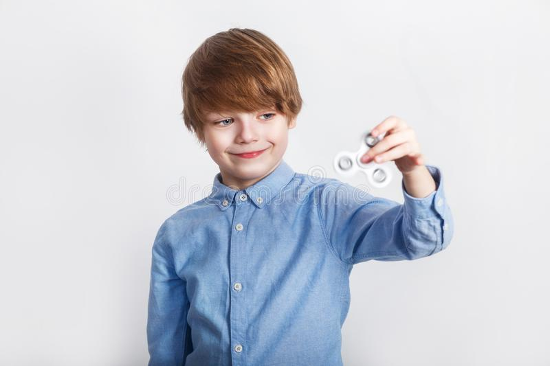 Young boy holding popular fidget spinner toy - close up portrait. Happy smiling child playing with Spinner. Young boy holding popular white fidget spinner toy stock photos
