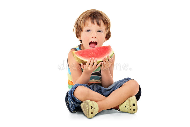 A young boy holding a slice of watermelon stock image