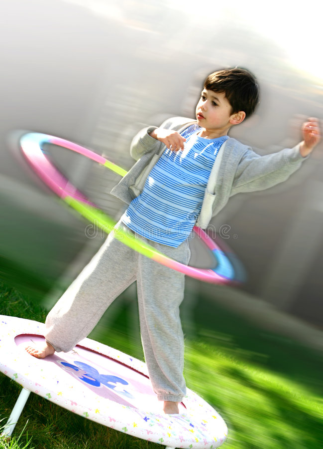 A young boy with a hoola hoop. A young boy enjoying himself outdoors with a hoola hoop while standing on a trampoline royalty free stock photo