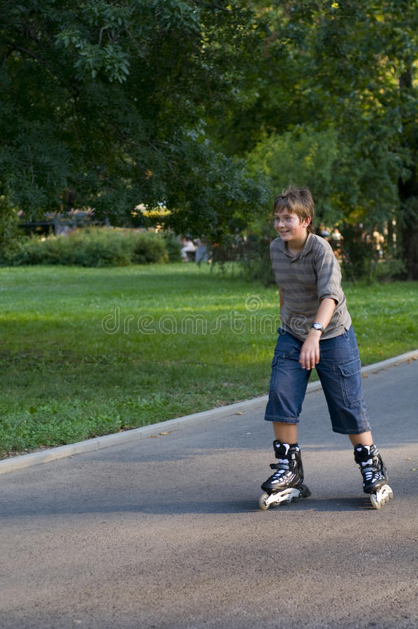 Young boy inline skating. In park, smiling stock photo