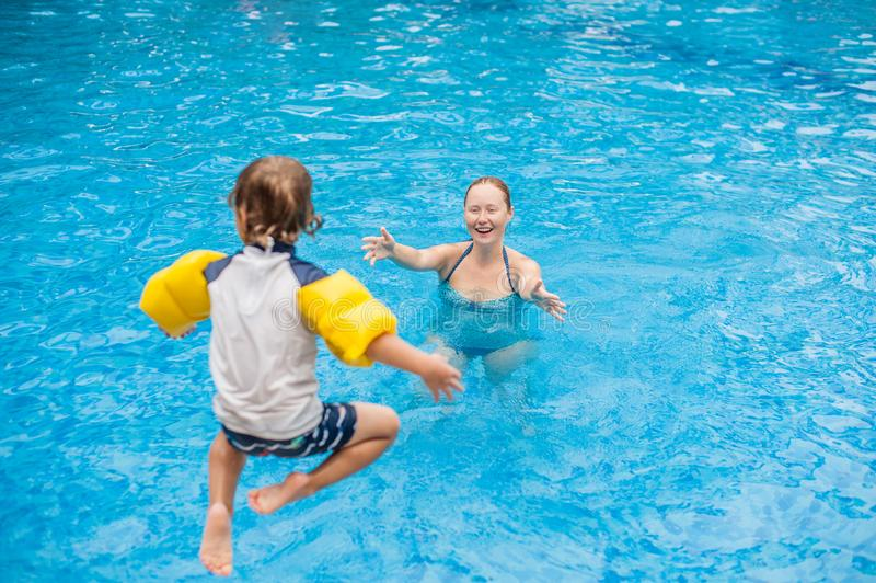 Young boy jump into the water of swimming pool stock photos