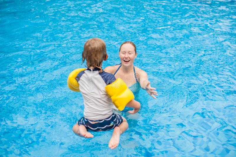 Young boy jump into the water of swimming pool stock images
