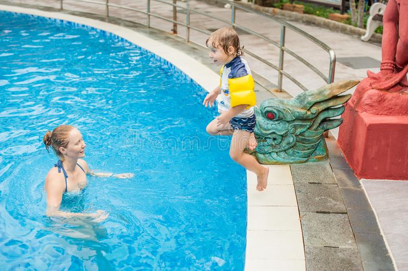 Young boy jump into the water of swimming pool stock photography