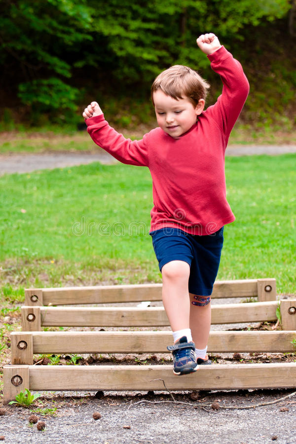 Young boy jumping over obstacle