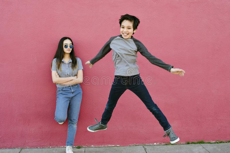 Young Boy Jumps High While His Teen Sister Watches Unimpressed Energetic. A teen sister looks onto her younger brother as he leaps into the air. She is stoic and stock image