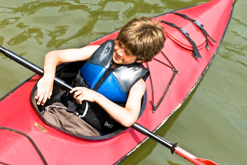 Young Boy in a Kayak. A cute young boy (10 years old) sitting in a red kayak getting ready to out on a ride stock photography