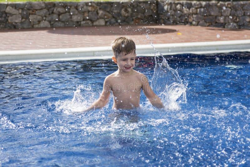 Boy plaiyng in swimming pool royalty free stock photo