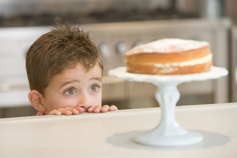 Young boy in kitchen looking at cake on counter royalty free stock images