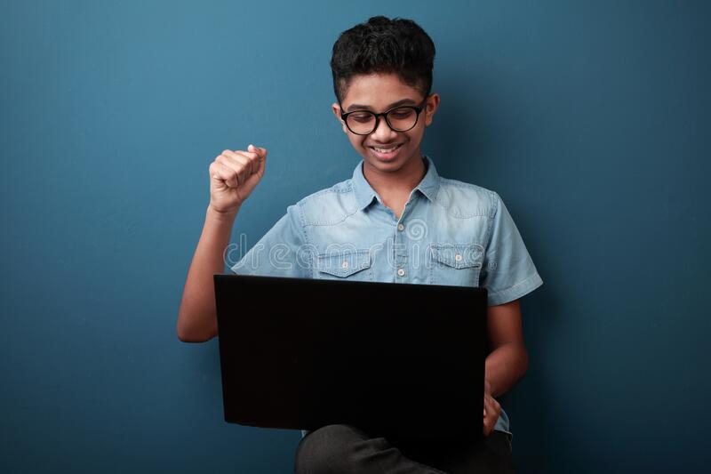 Young boy with laptop shows cheering gesture stock photo
