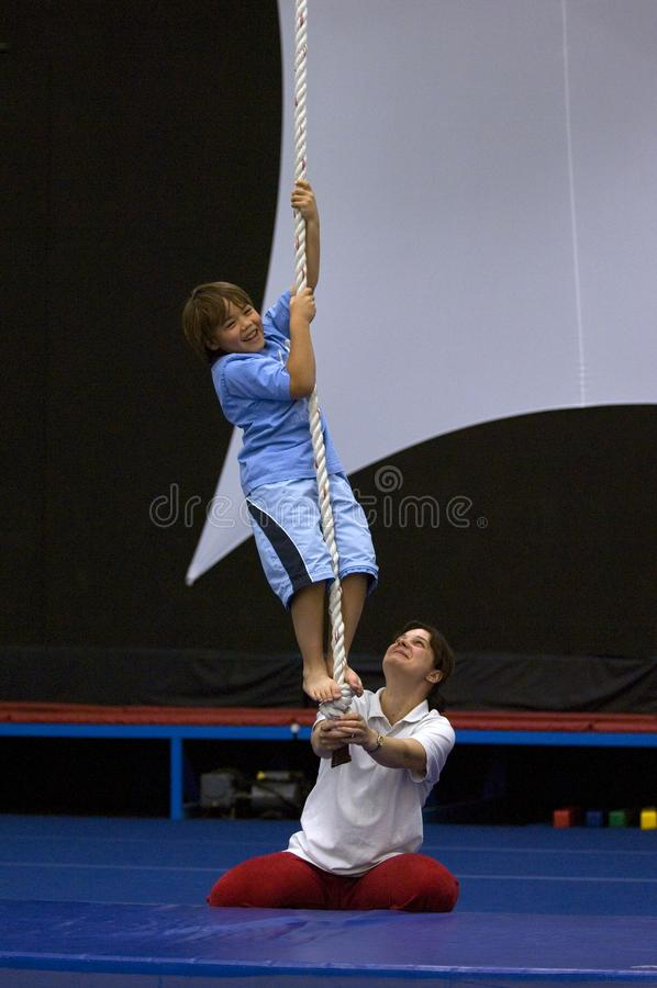 A young boy learns to climb a rope in n acrobat school. A young boy in blue learns to climb a rope in n acrobat school with the help of a female instructor royalty free stock photos