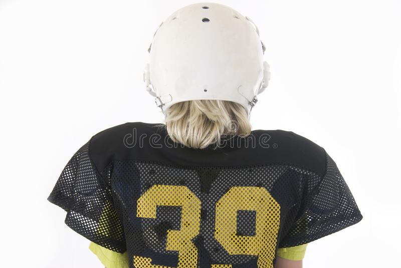 Young boy with long blonde hair in American football uniform royalty free stock photography