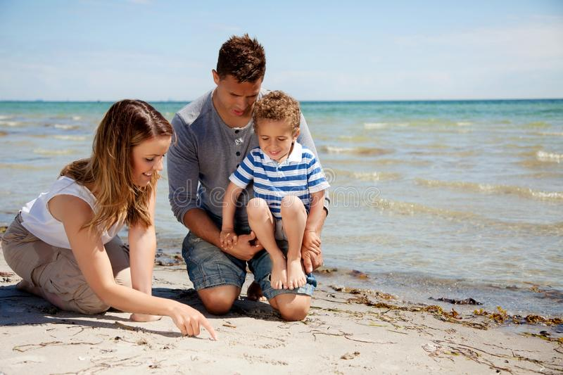 Young Boy Looking as His Mom Draws on the Sand stock photo