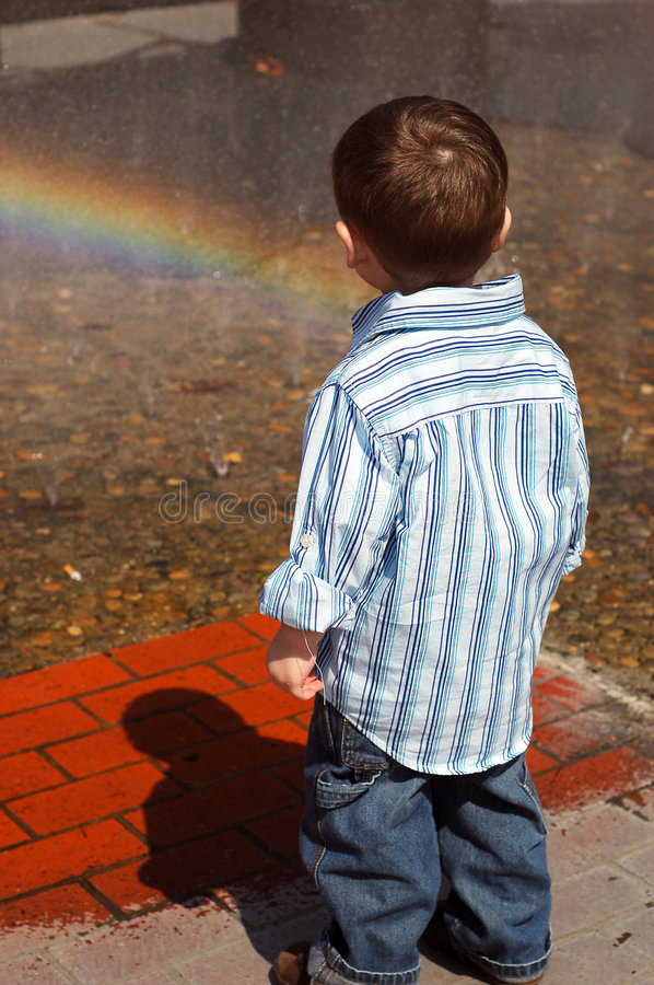Young Boy Looking into Fountain royalty free stock photos