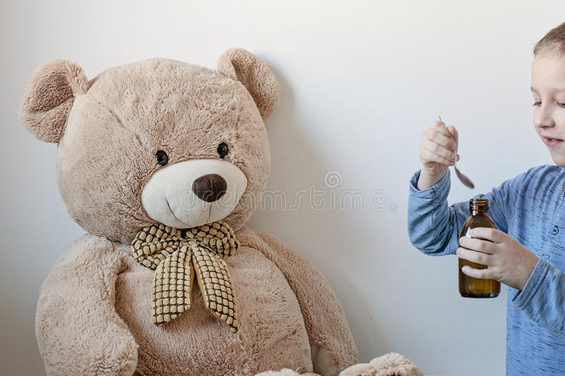 Young boy is looking after his big sick teddy bear. Boy is feeding him with medicaments in glass dark bottle from pharmacy. Medical theme. - Image royalty free stock image