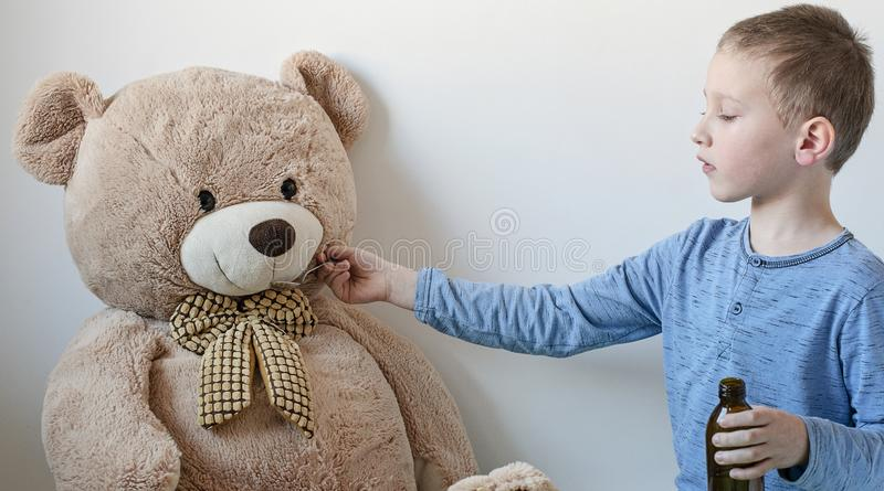 Young boy is looking after his big sick teddy bear. Boy is feeding him with medicaments in glass dark bottle from pharmacy. Medical theme. - Image stock photo