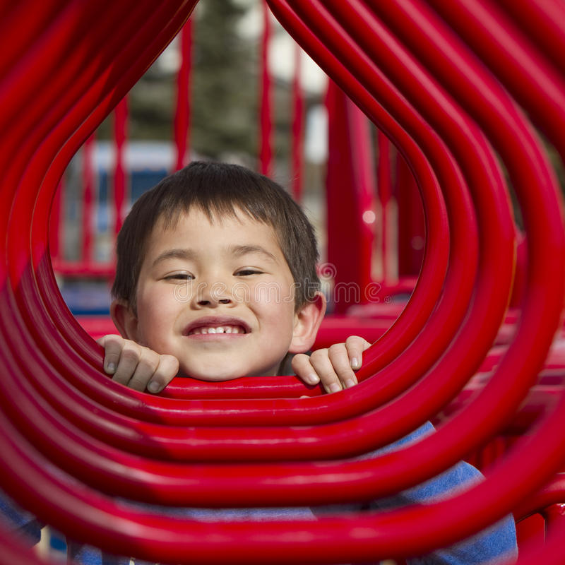 Young boy looking in the hoops of a playground. Cute young boy looking through the hoops of a playground structure stock image