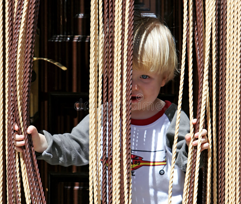 Download Young Boy Looking Out From Behind Curtain Stock Photos - Image: 123723