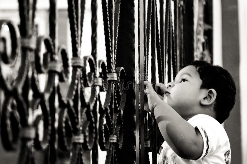 Young boy looks through the gaps of a metal gate in front my a Hindu Temple royalty free stock images