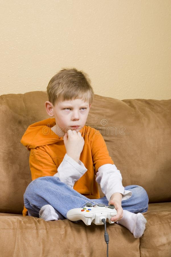 Young boy losing at video game stock images